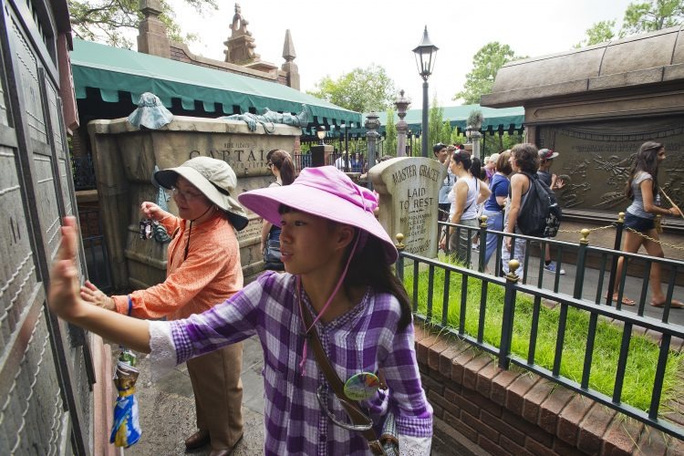 Magic Kingdom guests explore new interactive queue at the Haunted Mansion, where voices, music and other paranormal behaviors summon passersby.